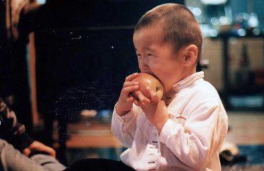 リンゴをにかぶりついているくりくり坊主の幼児が