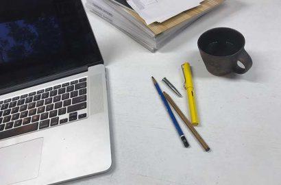 マックのノートパソコンと万年筆。鉛筆と陶製のコーヒーカップ